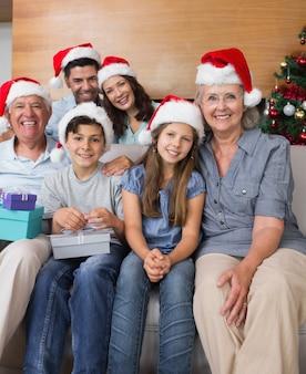 Família alargada em chapéus de natal com caixas de presente na sala de estar