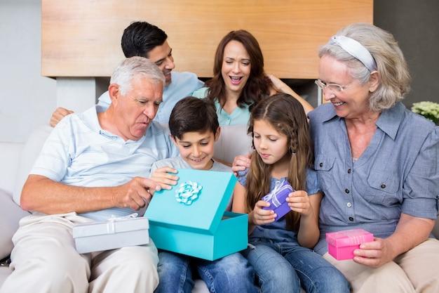 Família alargada sentada no sofá com caixas de presente na sala de estar