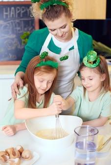 Família alegre assando na cozinha