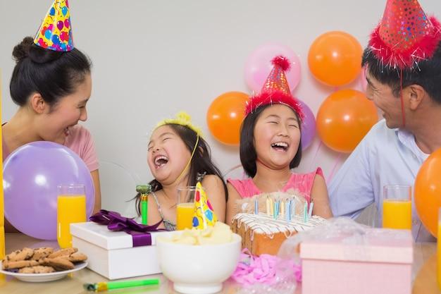 Família alegre com bolo e presentes em uma festa de aniversário