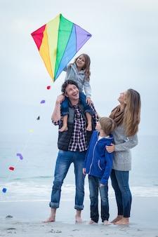 Família alegre com pipa na costa do mar