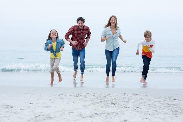 Família alegre correndo na praia contra o céu