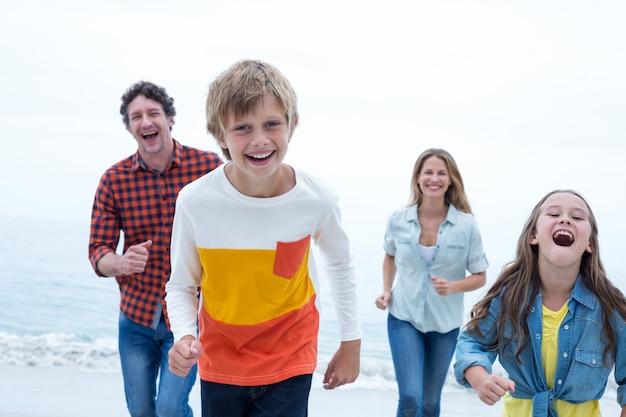 Família alegre correndo na praia