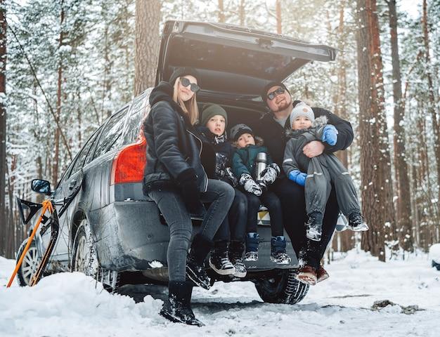 Família alegre de pai e mãe com seus filhos nas férias com o carro em madeira de inverno.
