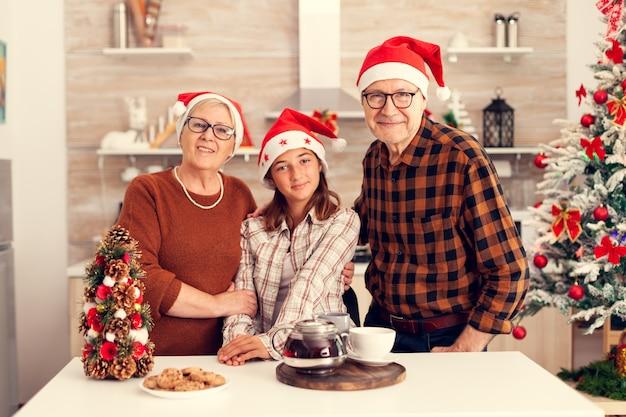 Família alegre de várias gerações usando chapéu de papai noel e aproveitando o natal