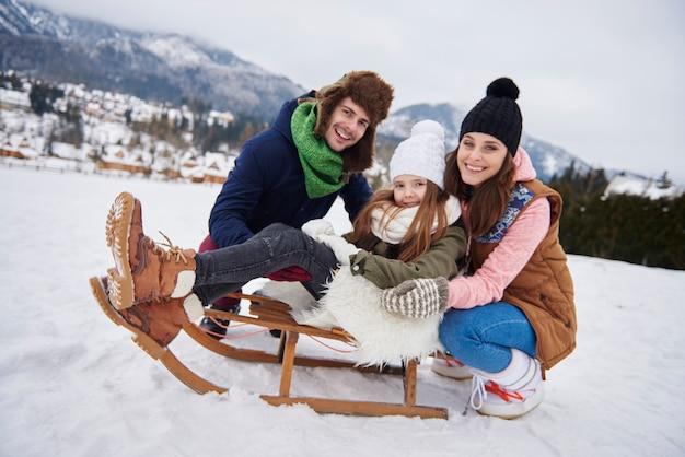 Família alegre desfrutando de andar de trenó na colina