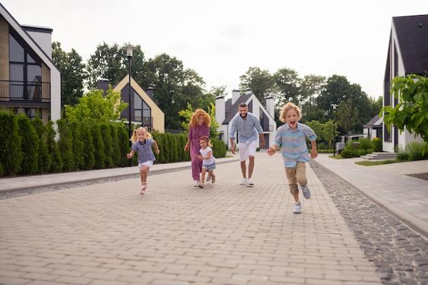 Família alegre e encantada correndo na rua