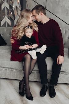Família alegre e jovial com bebê no sofá cinza