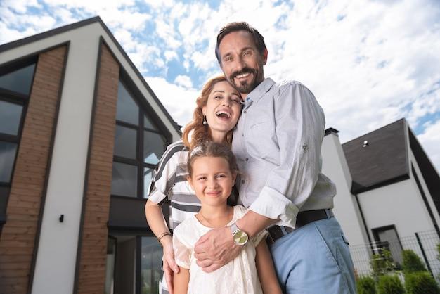 Família alegre e simpática olhando para você enquanto estão juntos