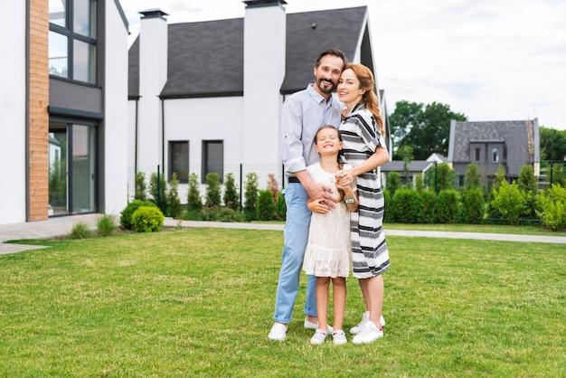 Família alegre e simpática sorrindo enquanto ficavam juntos na frente de sua casa