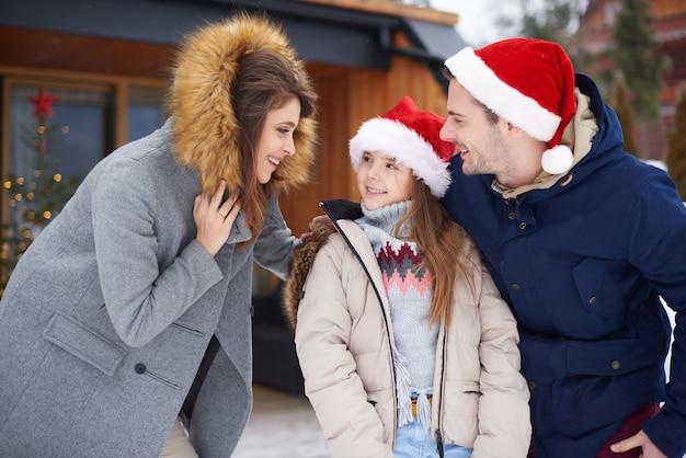 Família alegre em frente ao chalé Foto gratuita