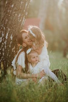 Família alegre em um parque, mamã e sua filha dois encantadora a sentar-se na grama quando olharem a câmera. família feliz, mãe e duas filhas.