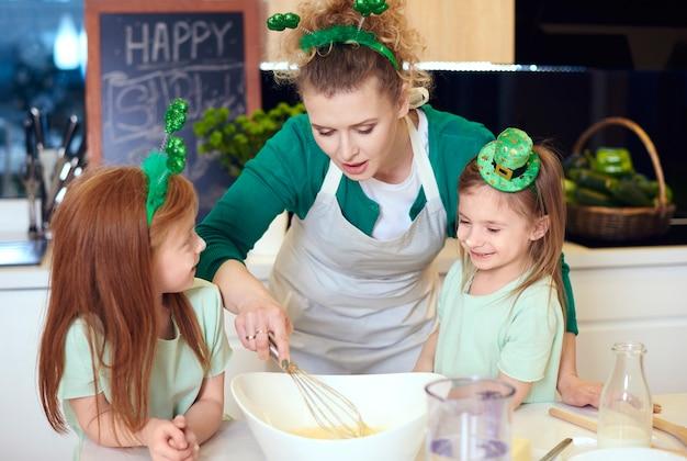 Família alegre fazendo biscoito ou bolinho juntos
