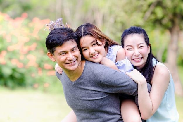 Família alegre fazendo piquenique relaxante juntos na natureza verde no parque