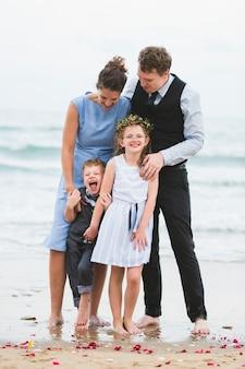 Família alegre na cerimônia de casamento de praia