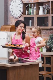 Família alegre na cozinha assar bolos ou cupcakes