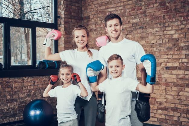 Família alegre no ginásio no equipamento de boxe.