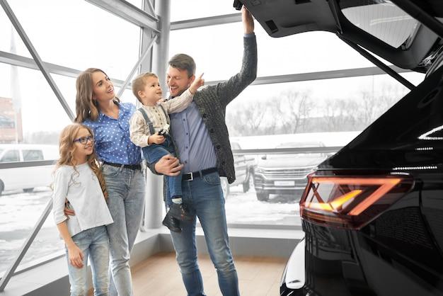 Família alegre, olhando para o grande porta-malas espaçoso do carro novo
