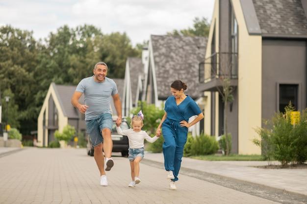 Família alegre. pais alegres e filha correndo enquanto passam o tempo fora à noite