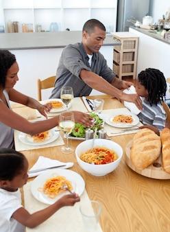 Família alegre que janta junto