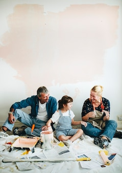 Família alegre relaxante depois de pintar as paredes