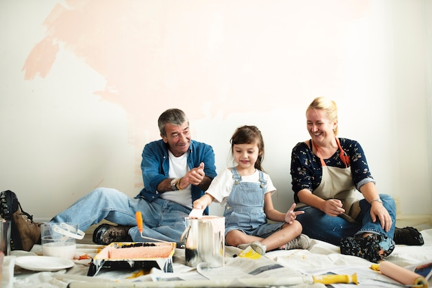 Família alegre relaxante depois de pintar o quarto