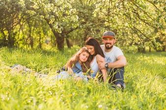 Família alegre sentado na grama verde durante o verão