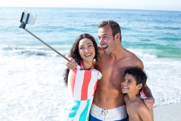 Família alegre tirando uma selfie na beira-mar
