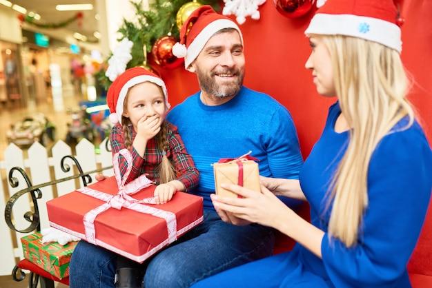 Família alegre, troca de presentes no shopping