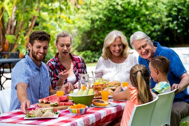 Família almoçando juntos no gramado