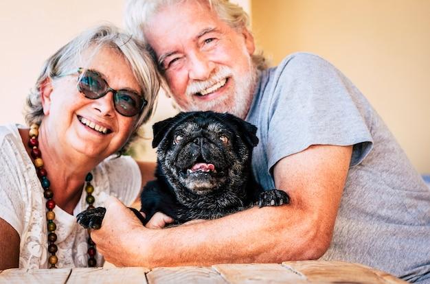 Família alternativa alegre com um casal idoso idoso e um cão pug preto engraçado se abraçando em uma atividade amorosa