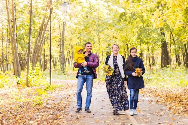Família ambulante com dois filhos no parque outonal.