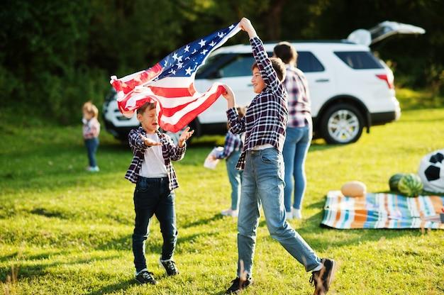 Família americana passando um tempo juntos. irmãos jogam com bandeiras dos eua contra um grande carro suv ao ar livre. celebrando a américa.