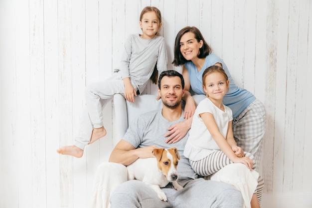 Família amigável de quatro membros: mulher morena alegre, seu marido, duas filhas e animal de estimação favorito