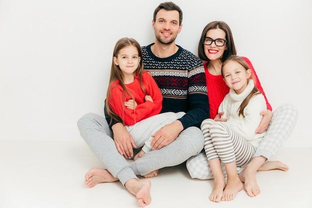 Família amigável feliz pose todos juntos contra branco