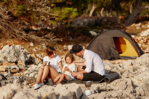 Família amigável, sentando-se perto da barraca no seacoast de pedra no dia.