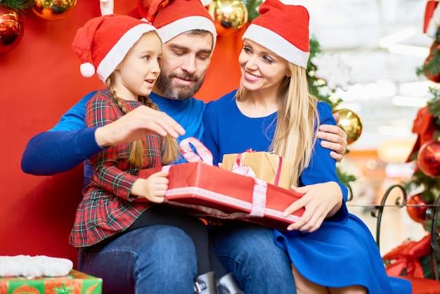 Família amorosa com presentes de natal no shopping