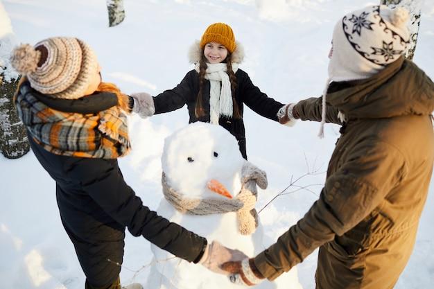 Família amorosa em torno de boneco de neve