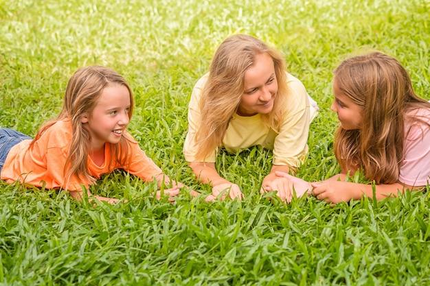 Família amorosa feliz está descansando no parque. mulher e os filhos da menina deitam-se na grama e conversam bem.