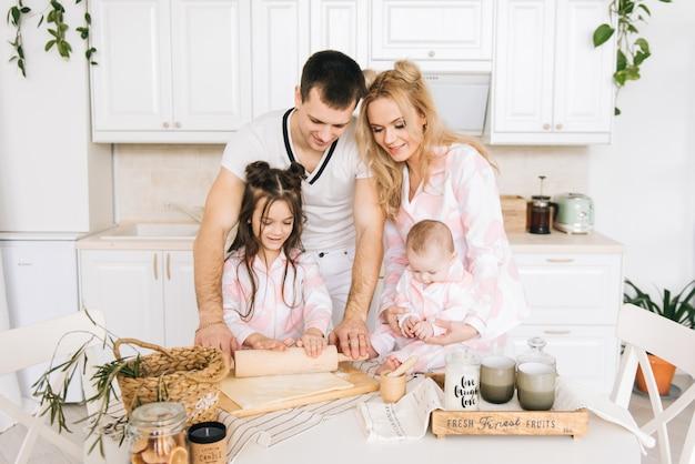 Família amorosa feliz está preparando padaria juntos. pai mãe e filha duas filha estão cozinhando biscoitos e se divertindo na cozinha. comida caseira e ajudante.