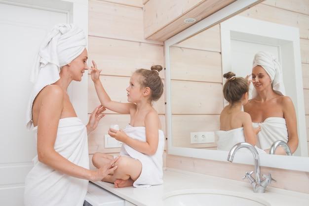 Família amorosa feliz mãe e filha com toalhas cuidam da pele e apliquem hidratante no rosto no banheiro branco.