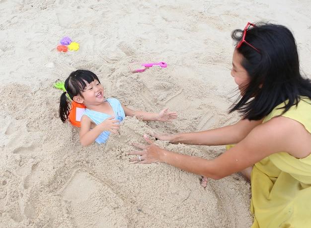 Família amorosa feliz mãe e sua filha criança menina jogando areia na praia