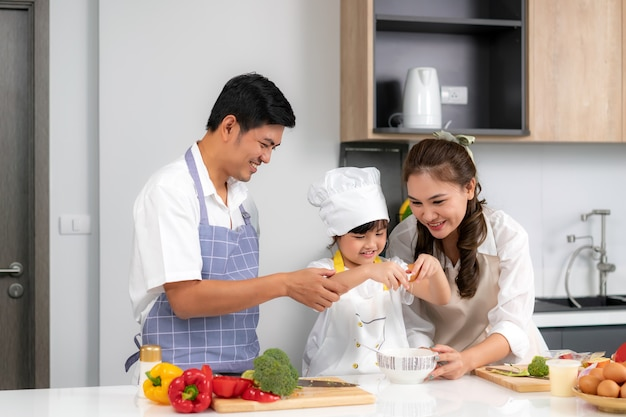 Família amorosa jovem asiática está preparando o jantar de comida na mesa da cozinha