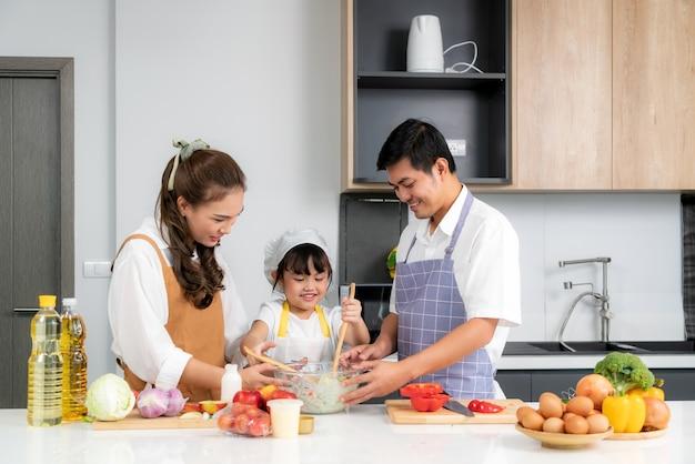 Família amorosa jovem asiática está preparando salada de legumes na mesa da cozinha