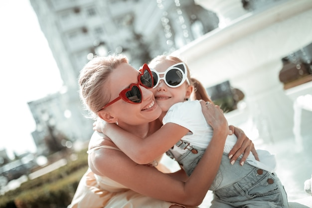 Família amorosa. mulher bonita feliz abraçando sua filha sorridente na frente da fonte branca do lado de fora.