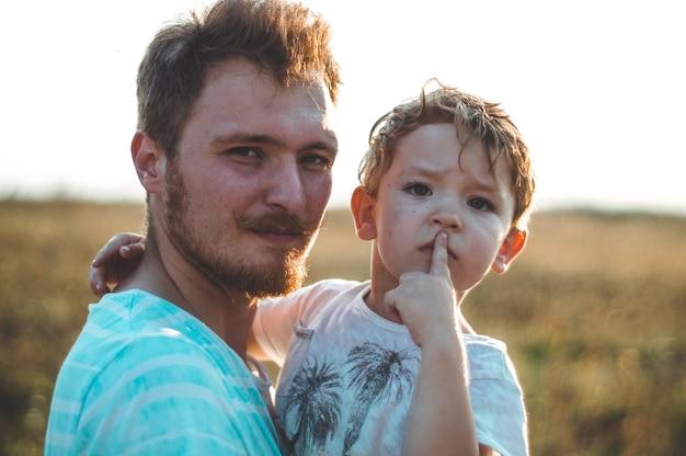 Família amorosa. pai e filho menino brincando e se abraçando ao ar livre. feliz pai e filho ao ar livre. conceito de dia dos pais.
