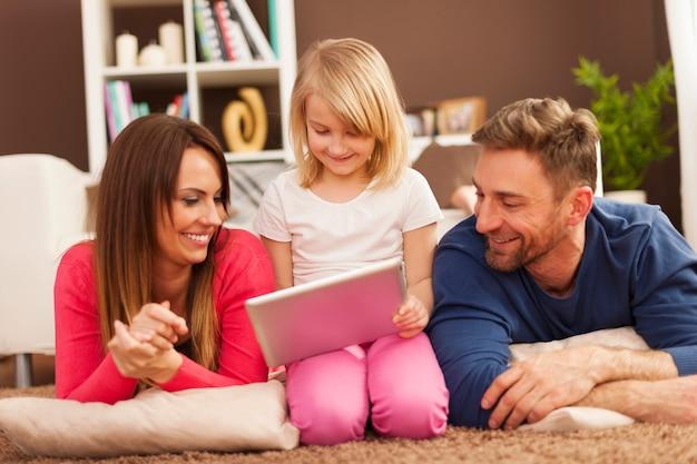 Família amorosa usando tablet digital no tapete
