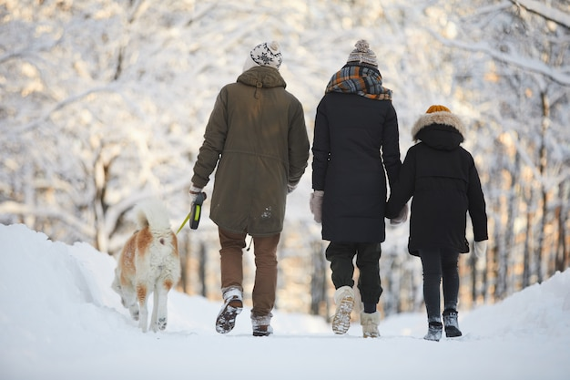 Família andando com cachorro no parque
