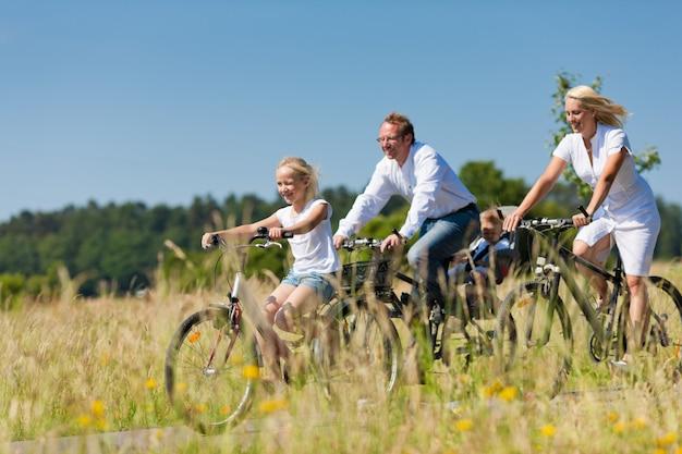 Família, andar de bicicleta ao ar livre no verão