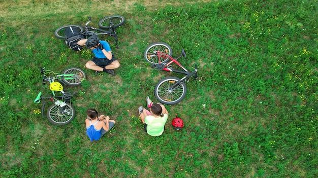 Família, andar de bicicleta em bicicletas ao ar livre vista aérea de cima, felizes pais ativos com criança se divertir e relaxar na grama, esporte familiar e fitness no fim de semana